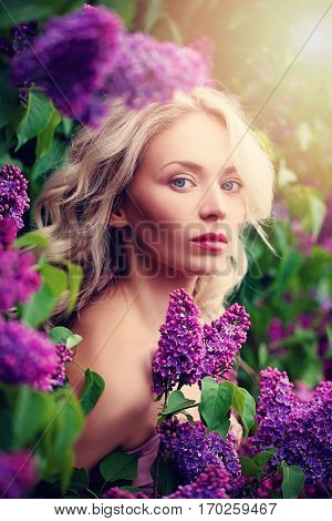 Pretty Blonde Woman with Healthy Skin and Blond Curly Hair. Beauty and Spring Flowers