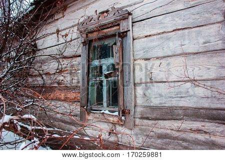 Facades Russian village of wooden houses in the old style. Old vintage weathered wooden window of ancient Russian house