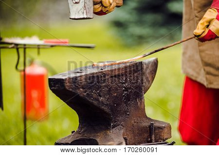 A smith forging a horse shoe on an anvil. blacksmith forges iron
