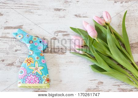 pink tulips with egg cozy on bright rustic wooden background