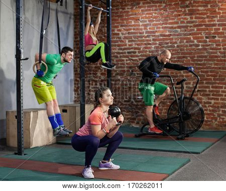 Two men and two women are training at the contemporary cross fit gym performing different exercises