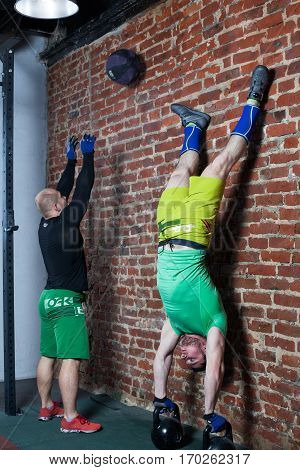 Two men are training against the red brick wall at the gym, one man is performing handstand on the kettlebells, the second is training with the medicine ball