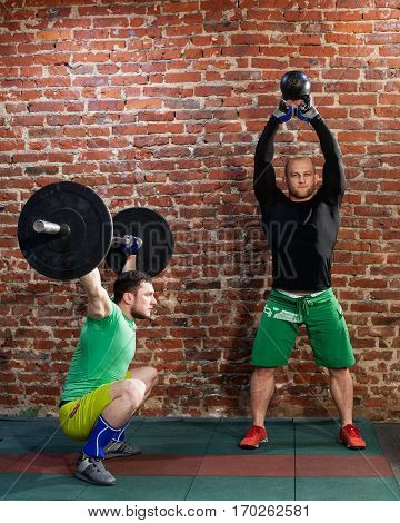 Two men are doing cross fit workout at the gym, one is lifting a barbell, the second is lifting a kettlebell against red brick wall