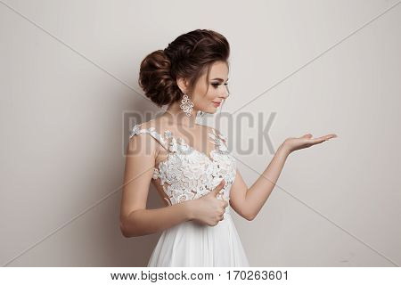 Gorgeous brunette bride holding something on hand gesturing super sign by big finger and showing by hand to side. Female wearing dress with stylish haircut and big earrings. White studio backgound.