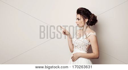 Side view of brunette woman posing at studio and pointing gesturing by finger at side looking away. Bride in wedding dress presenting something by hand to side. White background. Beauty concept.