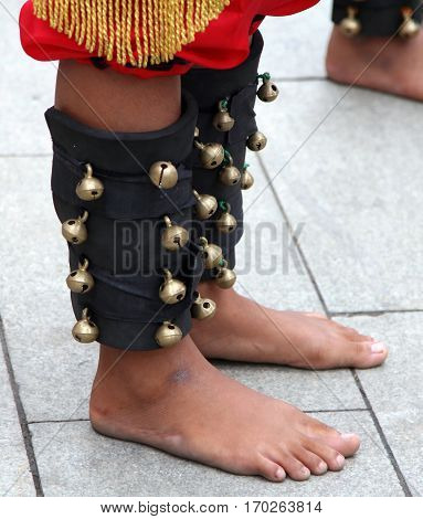 Traditional leather decoration with bells on the feet of Indonesian dancer