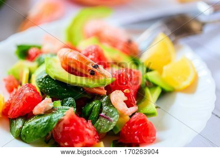 Bright salad with shrimp and fruit. Avocado and grapefruit. Bright background. Selective focus