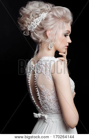 Rear view of pretty bride sensuality posing and turned away touching chin and face by hand. Blonde woman wearing lace dress with stylish haircut earrings with diamonds and accessories in hair.