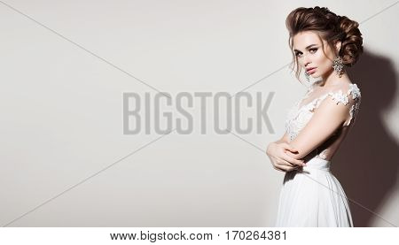Gorgeous girl wearing white wedding dress and stylish curly haircut posing at camera with crossed arms. Side view of brunette woman with big earrings and evening make up. Concept of beauty.
