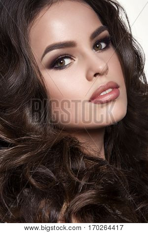 Portrait of beautiful brunette girl posing and looking at camera. Woman with long wavy hair plump lips and perfect skin. Professionally haircut long eyelashes and evening make up. Studio shot.