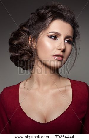Studio portrait of gorgeous brunette woman wearing red dress with big neckline. Girl sensuality posing looking and turned away. Female with perfect haircut and evening make up. Dark gray background.