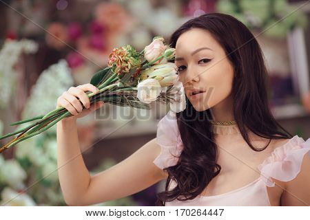 Beautiful girl in tender pink dress with bouquet flowers peonies in hands standing against floral bokeh background in flower shop. Joyful asian female holding bouquet near face. Playful fashion model looking at camera