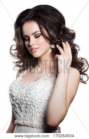 Portrait of brunette woman with long wavy hair wearing white wedding dress posing at studio. Female touching hair by hand sensuality posing with closed eyes. Girl with plump lips and evening make up.