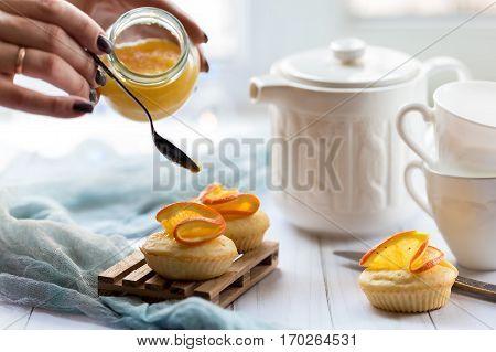 orange cupcakes female hands orange jam teapot and cups