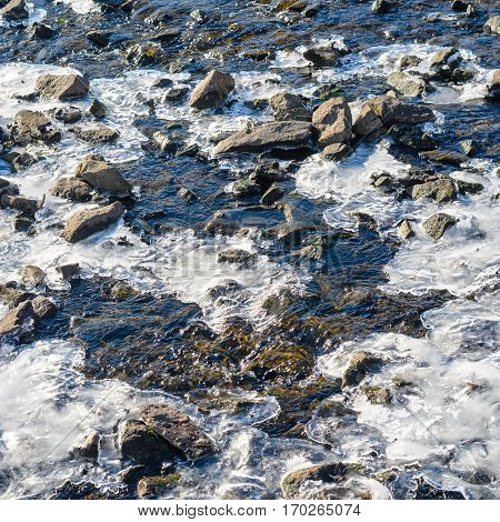 Spring melting of snow and ice. River rapids with rocks and icy patches