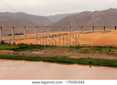 Bridge over Yellow river (Huang He) in Tengger desert Shapotou district China