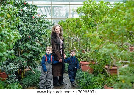 Mother And Children walking in azalea orangery or Greenhouse.