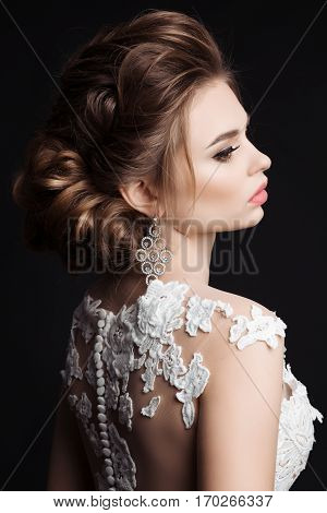 Gorgeous brunette girl posing at studio with closed eyes looking down. Woman after beauty salon with stylish haircut and evening make up. Female wearing white dress and big earrings.