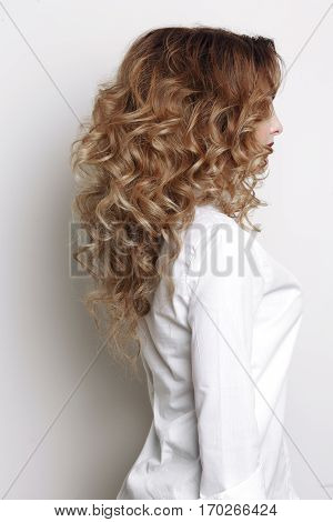 Side view of incognito curly woman with long hair and stylish volume haircut turned away. Girl after beauty salon wearing in white shirt posing at studio.