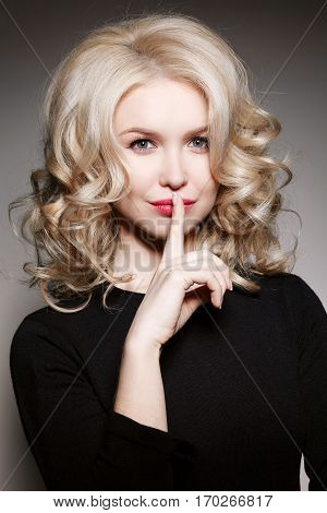 Portrait of curly gorgeous blonde girl in black blouse holding finger on lips and gesturing sign of silence. Posing and looking at camera. Gray studio background.