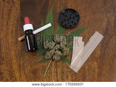 Cannabis sativa weed leaf and flower buds on wooden background with grinder THC oil and large smoking paper.
