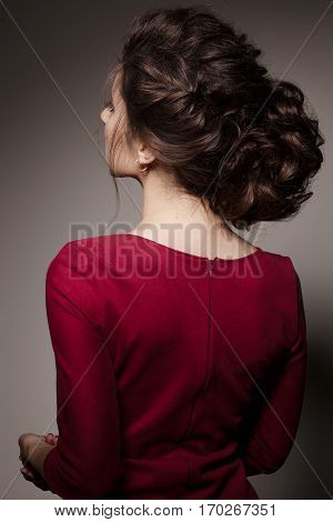 Back view of brunette woman with stylish haircut of curly hair turned back posing with crossed arms. Brunette girl posing in dark studio wearing red dress. Gray studio background.