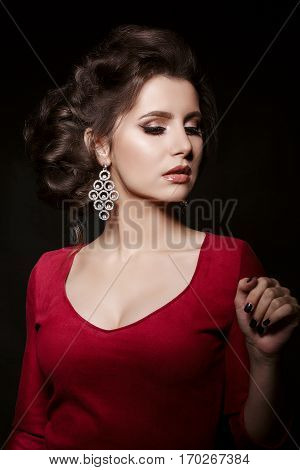 Front view of seductive brunette girl wearing red dress and big earrings. Woman with perfect make up and stylish haircut posing in dark studio gesturing by hand and looking down.