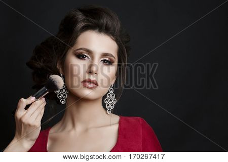 Brunette woman in red dress seductive posing at studio when incognito makeup artist making blush on cheekbone with brush. Unhappy girl with stylish haircut and big earrings.