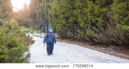 Winter portrait of kid boy in colorful clothes outdoors. Active outoors leisure with children in winter on cold snowy days. Happy toddler child having fun with snow in forest