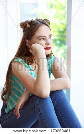 Sad teenage girl sitting near window