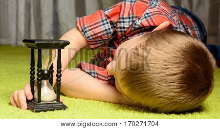 little boy lying on the floor and looking at hourglass