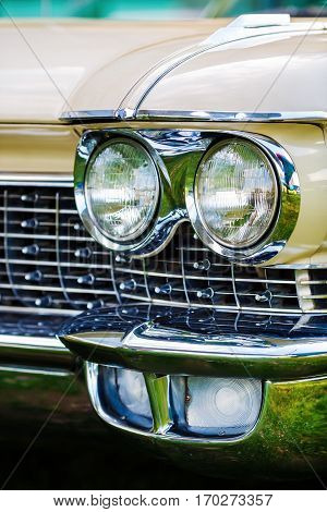Minsk Belarus - May 07 2016: Close-up photo of beige Cadillac de Ville 1959 model year. Headlight of vintage car. Close-up detail of retro auto. Shallow depth of field. Selective focus.