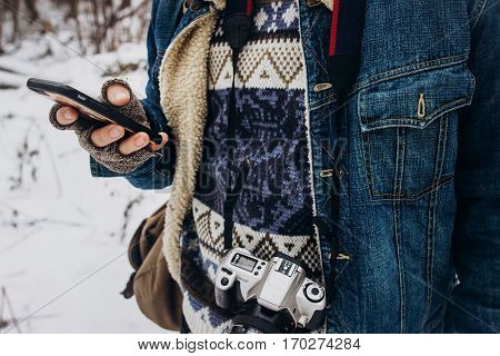 stylish hipster traveler holding phone and browsing traveling and exploring snowy forest with photo camera. young photographer. wanderlust and adventure concept