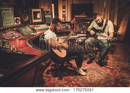Two professional guitarists performing in boutique recording studio.