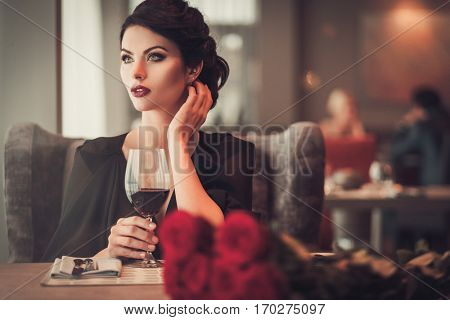 Elegant brunette lady with glass of red wine in restaurant.
