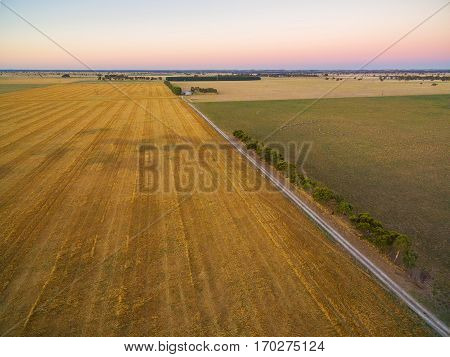 Aerial View Of Harvested Field And Green Pasture At Sunset In Australia.