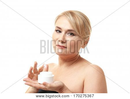 Mature woman with jar of anti-aging cream on white background
