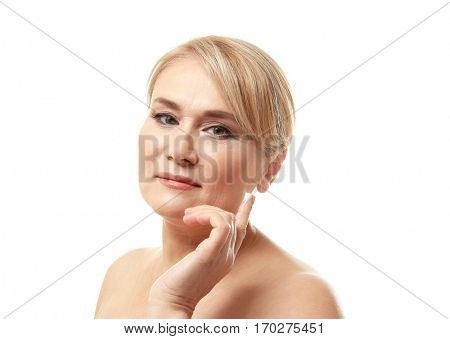 Mature woman applying anti-aging cream onto face, on white background