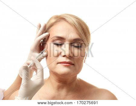 Mature woman receiving filler injection on white background