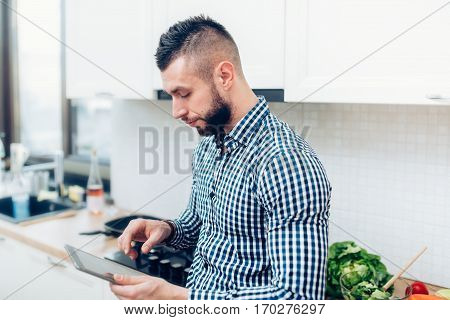Cheerful Man Cooking In New Kitchen, Using Tablet For Receipes And Looking On Internet