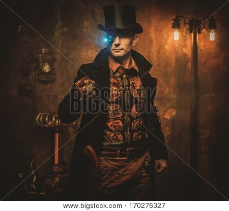 Portrait of steampunk man with various mechanical devices on vintage steampunk background.