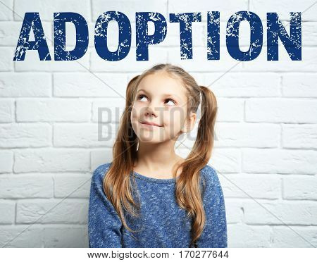 Adoption concept. Happy little girl on brick wall background