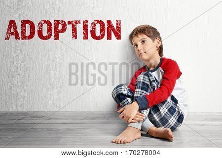 Adoption concept. Sad little boy sitting on floor near wall