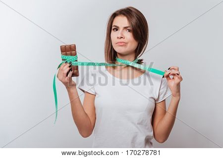 Image of young lady standing over white background while holding centimeter and chocolate