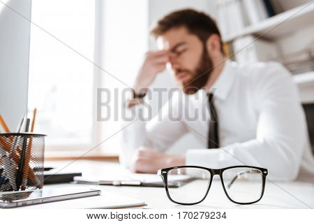 Image of confused young businessman sitting in office near computer and glasses. Focus on glasses.