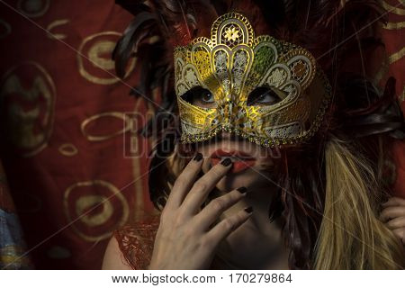 Sexy, Beautiful blond woman with mysterious mask with red feathers. The background has floral motifs in garnet and gold