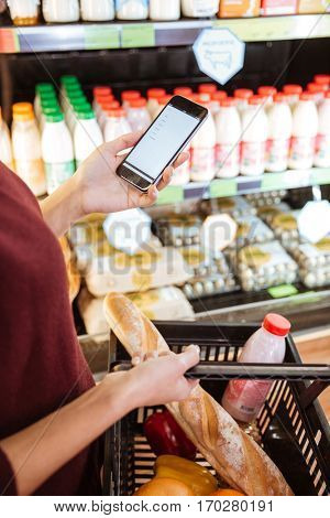 Closeup of woman with basket doing shopping and using mobile phone in grocery shop