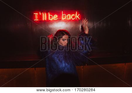 Stylish young woman in fur coat standing over background with glowing inscription I'll be back