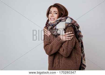 Young Freeze woman in sweater and scarf looking at camera. Isolated gray background
