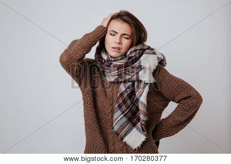 Pensive woman in sweater and scarf holding her head. Isolated gray background